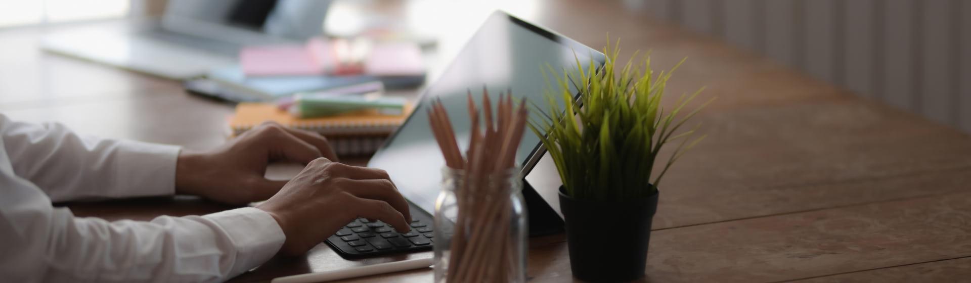 Manos de una persona trabajando delante de un portátil/tablet