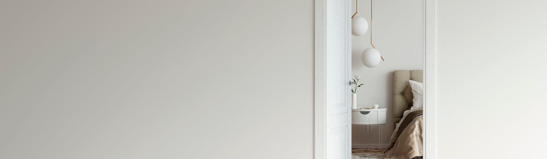 Puerta de dos batientes abierta en medio de una pared blanca
