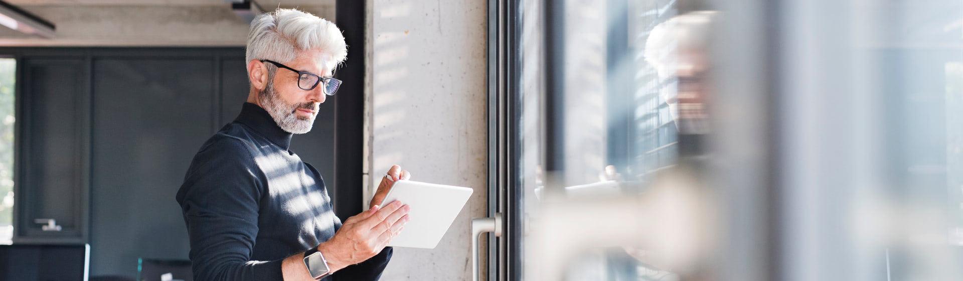 Una hombre mirando su tablet, de pie junto a una ventana
