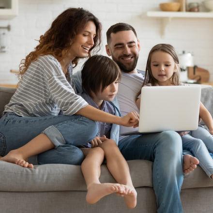 Família sentada en un sofá, mirando un portátil
