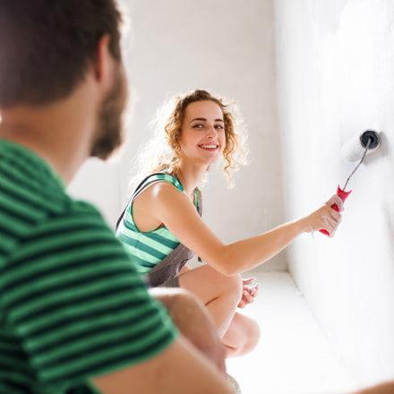 Chica pintando una pared con un rodillo que mira cámara