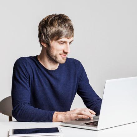 Chico sentado mirando su portátil