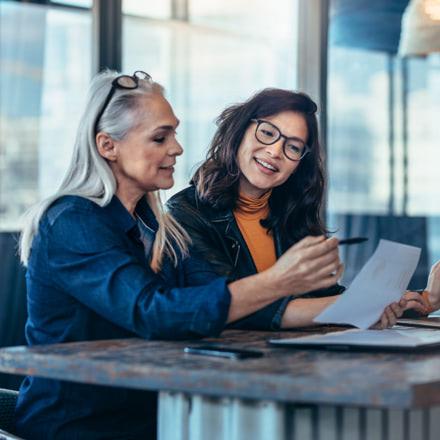 Dos mujeres comentando los datos de un informe frente a un portátil