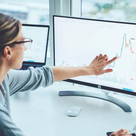 Mujer señalando a unos gráficos en una pantalla
