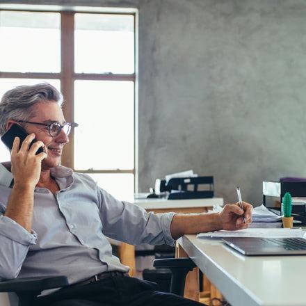 Hombre hablando por el móvil sentado en una silla frente a un escritorio